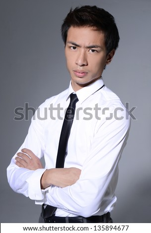 Friendly and smiling businessman looking at camera with reliability isolated on gray background - stock photo