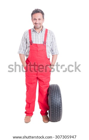 Friendly and trustworthy mechanic standing with hands in pockets newa a wheel tire isolated on white - stock photo