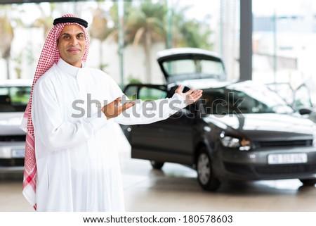 friendly arabian car salesman doing welcoming gesture - stock photo