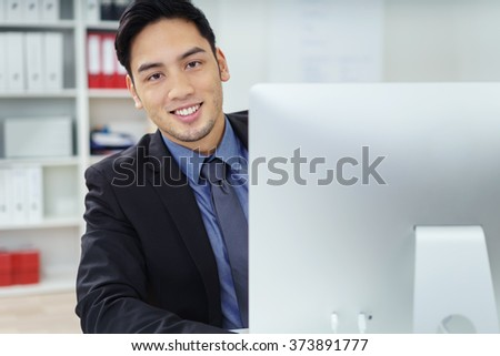 Friendly Asian businessman looking around the side of his desktop monitor to smile at the camera a he sits at his desk in the office - stock photo