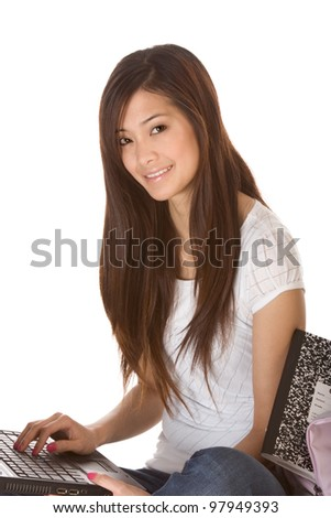 Friendly Asian High school girl student sitting in jeans with portable laptop PC computer - stock photo