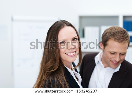 Friendly attractive businesswoman looking at the camera with a man colleague behind her, head and shoulders portrait - stock photo