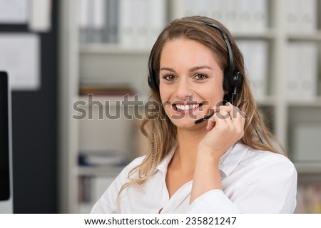 Friendly attractive call center operator smiling at the camera with a lovely friendly call as she takes a call on her headset in the office - stock photo