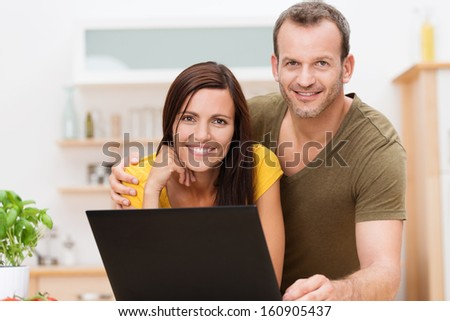 Friendly attractive young couple working on a laptop together in the kitchen or living room posing together arm in arm smiling for the camera - stock photo