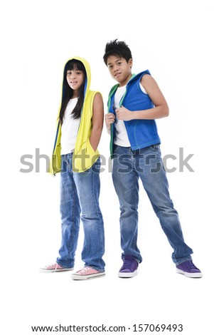 Friendly attractive young teenage siblings standing sideways facing each other in casual tops with their arms folded looking at the camera isolated on white - stock photo