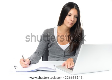 Friendly attractive young woman working at a desk with her laptop computer writing notes in a notebook conceptual of a hardworking office worker or businesswoman, or a student studying by e-learning - stock photo