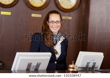 Friendly beautiful stylish young receptionist standing behind a counter in a hotel lobby with a welcoming smile - stock photo
