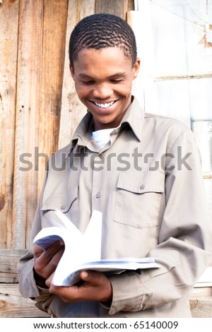 Friendly black student paging through his book. - stock photo