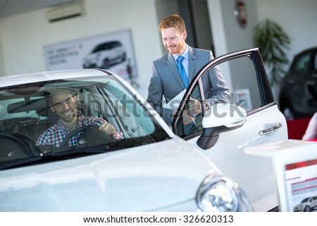 friendly car dealer showing new car to male customer  - stock photo