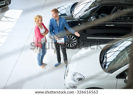 Friendly car dealer showing young women new car in showroom - stock photo