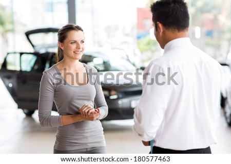 friendly car salesman talking to a young woman inside showroom - stock photo