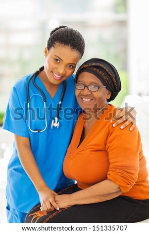 friendly caring young african nurse and senior patient  - stock photo