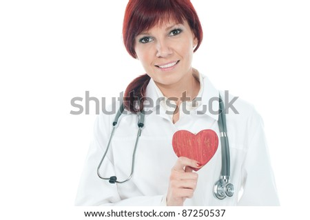 Friendly caucasian female cardiologist with a red wooden heart in her hands, over a white background - stock photo
