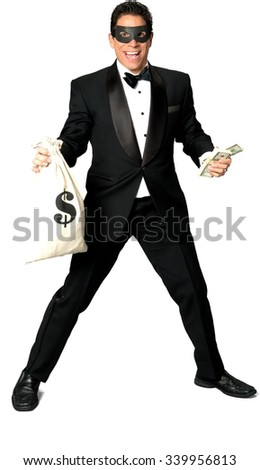 Friendly Caucasian man with short black hair in a tuxedo and mask holding bag of money - Isolated - stock photo