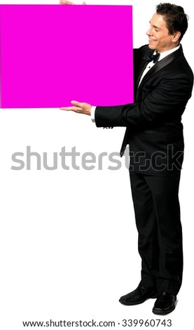 Friendly Caucasian man with short black hair in a tuxedo holding large sign - Isolated - stock photo