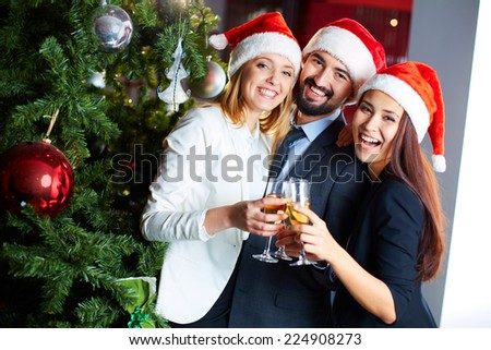 Friendly co-workers in Santa caps toasting with champagne by Christmas tree in office - stock photo