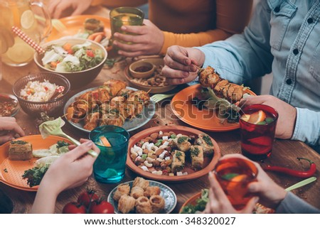 Friendly dinner. Top view of group of people having dinner together while sitting at the rustic wooden table - stock photo