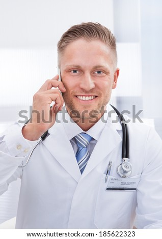 Friendly doctor chatting on his mobile phone smiling as he listens to the conversation  close up of his face - stock photo