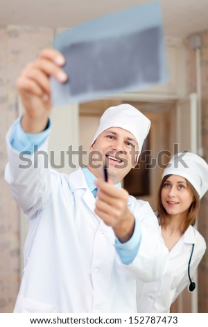 friendly doctors looking x-ray scan in clinic - stock photo