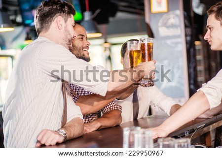 Friendly evening. Three cheerful friend clink beer at the bar and drink a beer while the bartender is standing on the bar. Friends having fun together - stock photo