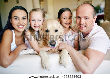 Friendly family members and their pet resting on sofa at home - stock photo