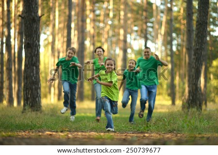 Friendly family running together in autumn park - stock photo