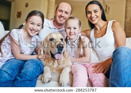 Friendly family with dog having rest at home - stock photo
