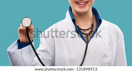 Friendly female doctor - isolated over a blue background - stock photo