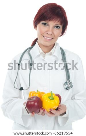 Friendly female doctor smiling and holding fresh vegetables and fruits – isolated over white - stock photo