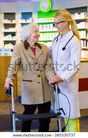Friendly female doctor with blond pony tail standing with elderly woman using walker in front of pharmacy counter - stock photo