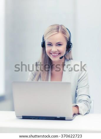 friendly female helpline operator with laptop - stock photo