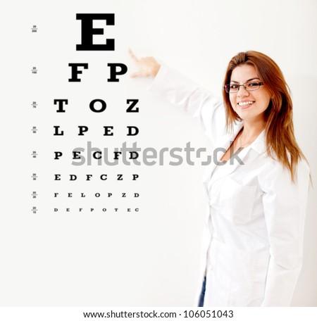 Friendly female optician making an eye exam - stock photo