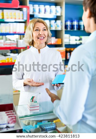 Friendly female pharmacist counseling customer about drugs usage in modern farmacy - stock photo