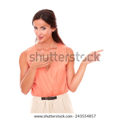 Friendly female pointing to her left while looking at you smiling in white background - copyspace - stock photo