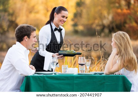 friendly female waitress pouring wine for romantic couple outdoors - stock photo