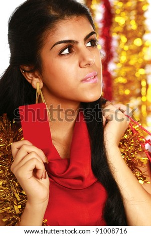 Friendly girl showing blank business card isolated on christmas decorated background - stock photo