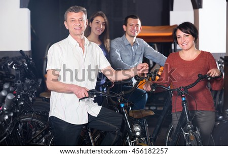 Friendly happy young and mature couples hiring bicycles ot rental store - stock photo
