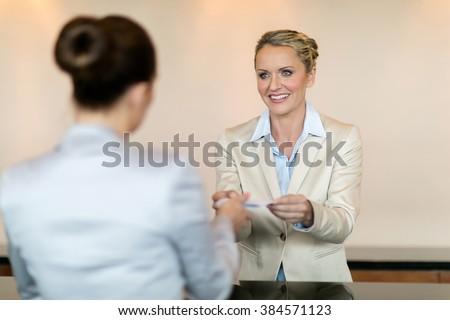 friendly hotel receptionist handing over key to customer - stock photo