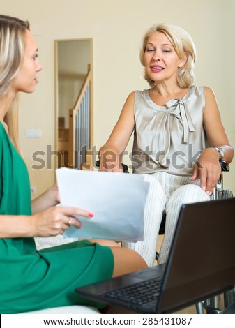 Friendly insurance agent and mature disabled woman on chair indoor - stock photo