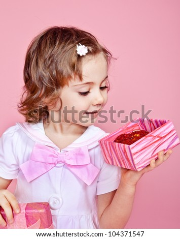 Friendly little girl opening present box - stock photo