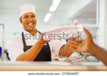 friendly male butcher selling packed meat to customer in butchery - stock photo