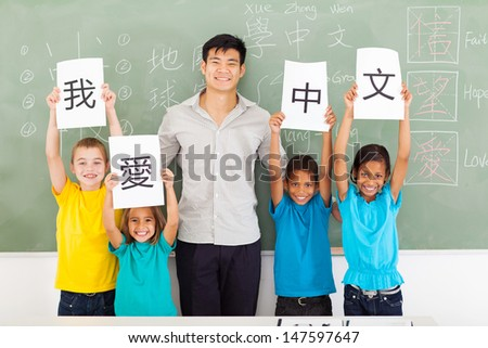 friendly male chinese teacher with group multiracial primary students holding papers saying i love chinese - stock photo