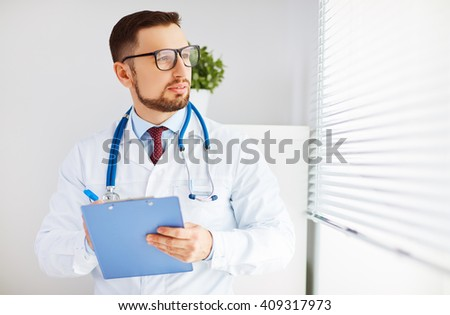 friendly male doctor in his office at the clinic - stock photo