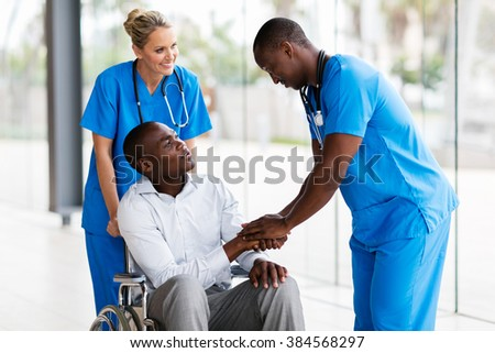 friendly male medical doctor handshaking with handicapped patient - stock photo