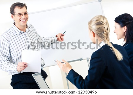 Friendly man standing at whiteboard and pointing at something on it while looking at smart women - stock photo