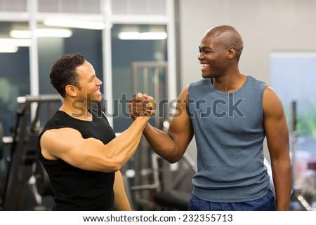 friendly men handshaking in gym - stock photo