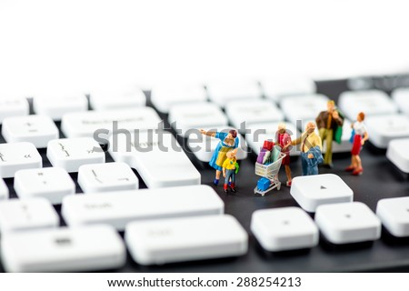 Friendly miniature family looking at computer keyboards. Technology concept. Macro photo - stock photo