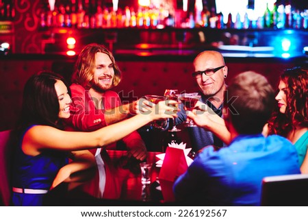 Friendly people toasting with alcoholic drinks while sitting in the bar - stock photo