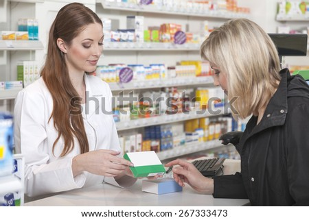 Friendly pharmacist recommends a product to her customer - stock photo
