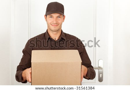 Friendly postman having a packet for you - stock photo